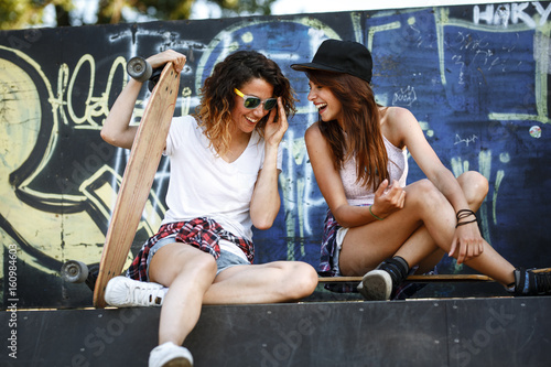 Fotobehang Skateboard Two female skaters friends sitting on ramp and hangout at the skate park .Laughing and fun.