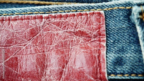 Closeup detail of blue denim jeans with red leather label, as background. Dolly sliding shot 4K ProRes HQ codec