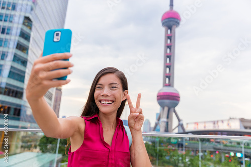 Asian tourist girl taking a selfie smartphone picture at a famous Shanghai landmark in the financial district of Pudong in China Poster