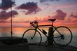 Silhouette of a bike standing beside a dock by the beach with a sunset background