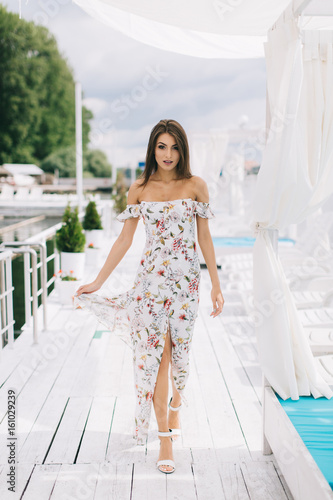 Plakát Portrait of a beautiful woman in a dress posing on a white wooden beach of summer