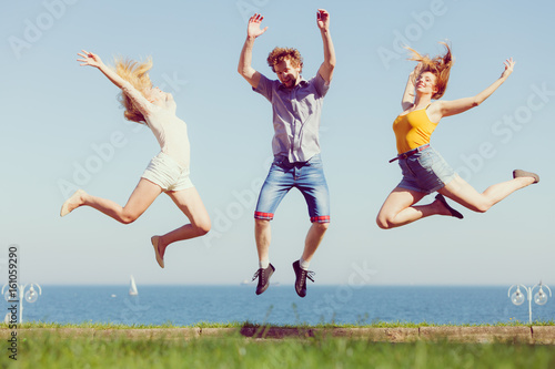 Group of friends boy two girls jumping outdoor