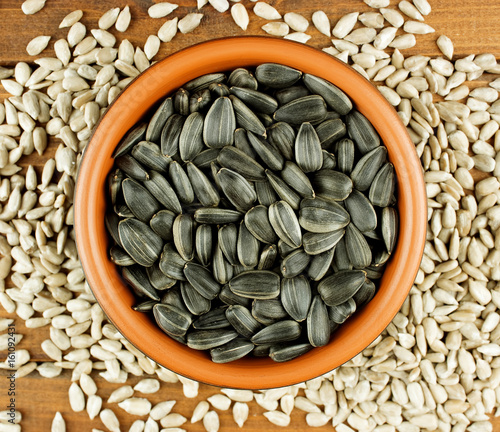 sunflower seeds in the small bowl on the wooden background