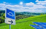 Fototapety Wegweiser zur Solartankstelle für Autos vor traumhafter Landschaft mit strahlender Sonne - Trafic sign to the solar station for cars in front of a wonderfull landscape with a bright sun
