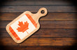Concept of Canadian cuisine. Cutting board with a Canada flag on a wooden background