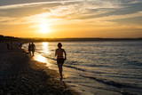 People walking and jogging along Gdansk city beach in Jelitkowo under setting sun. Gdańsk, Poland, 19.06.2017
