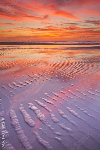 Beautiful sunset and reflections on the beach at low tide