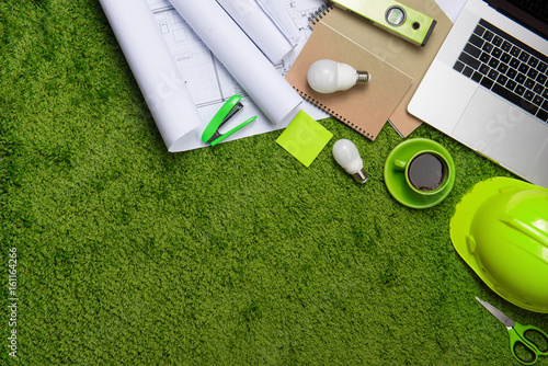 Workplace with helmet, blueprints, laptop and notepad on grass background Poster