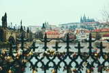 View of Vltava river, Prague castle, Mala Strana and Charles Bridge from the other side of the river over the fence with love locks. ancientarchitectureattractionbaroquebeautifulbridgebuildingcapital