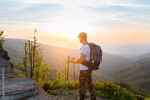 Man tourist with trekking poles watching beautiful sunrise Poster