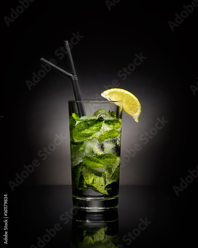 Mojito cocktail with a slice of lime and ice on a black background.