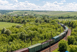 The freight railroad train rides through fields and hills amidst green meadows and trees