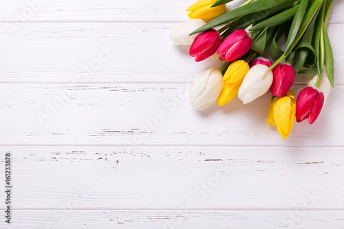 Yellow, pink and white tulips flowers on vintage wooden background.