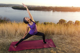 Gorgeous fit woman doing yoga exercises by the river at sunset, beautiful scenery, city in background