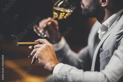 Young man tasting white wine and smoking cigar Poster