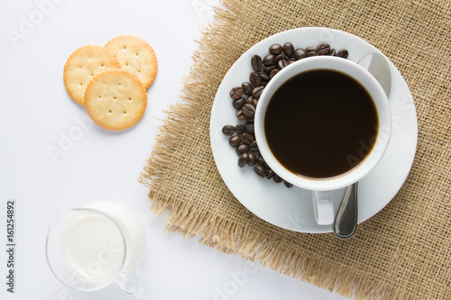 Cup of coffee and milk with biscuit on wooden table