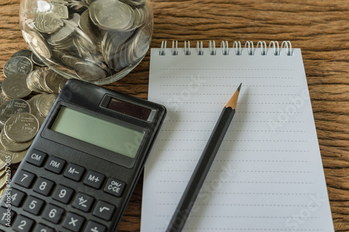 selective focus on pencil and note book with stack of coins and calculator on wood table as financial saving concept