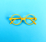 Fototapety A pair of round glasses on a bright blue background