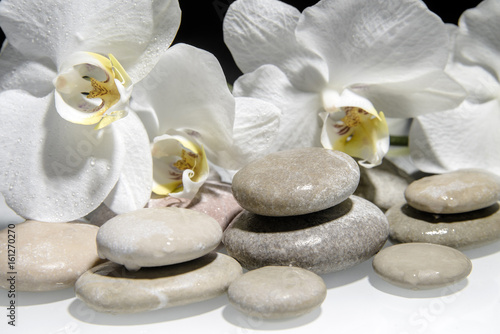 Papiers peints Spa flat stones on a white glass on the background of white orchids