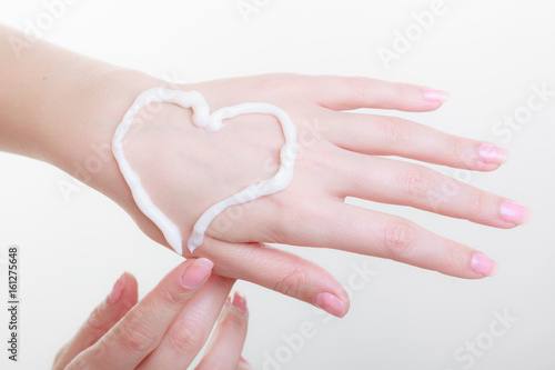Cream on woman hand, heart shape Poster