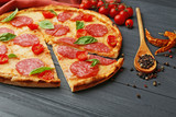 Pizza with salami on wooden background