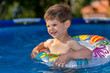 young boy playing in swimming pool wirh float ring