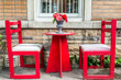 Red chairs and table with flowers in outside garden patio