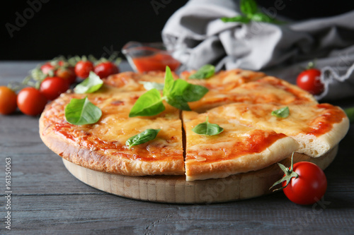 Tasty sliced pizza with basil leaves, closeup