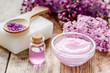 lilac cosmetics with flowers and spa set on wooden table background