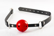 Fetish and kinky sex play and BDSM sex toys concept with a red ball gag toy isolated on white