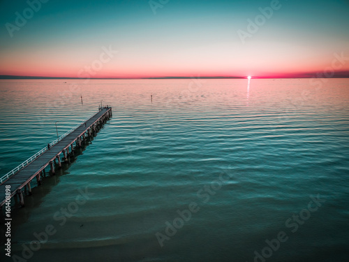 Plagát Long wooden pier stretching into the ocean at beautiful sunset