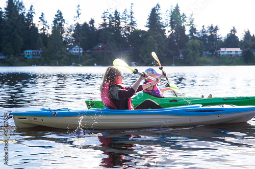 Poster two kids racing on a lake in kayaks