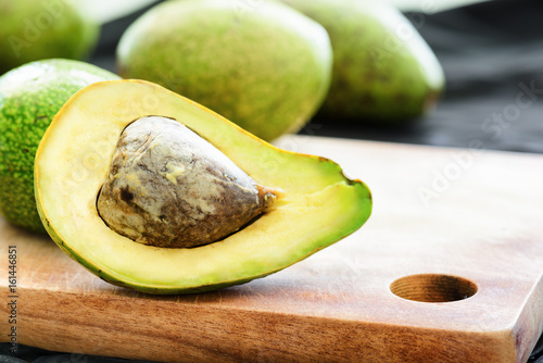 Closeup view of fresh ripe avocado on wooden cutting board
