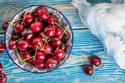 Fresh cherries in a blue bowl. - 161476431