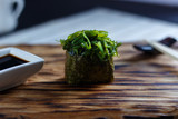 Appetizing one sushi gunkan with with greens chuka or seaweed served on wooden rustic table, flat lay. Japanese cuisine, traditional food