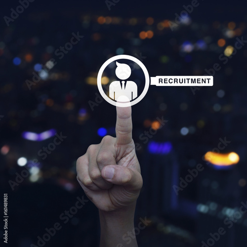 Hand pressing businessman with magnifying glass icon over blur colourful night light city tower, Business recruitment concept