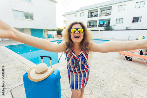 Travel, summer holidays and vacation concept - Happy woman near pool area with suitcase.