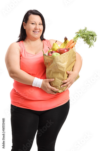 Overweight woman holding paper bag filled with fruit and vegetables Poster