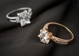 two jewelry rings with diamonds on black cloth, soft focus