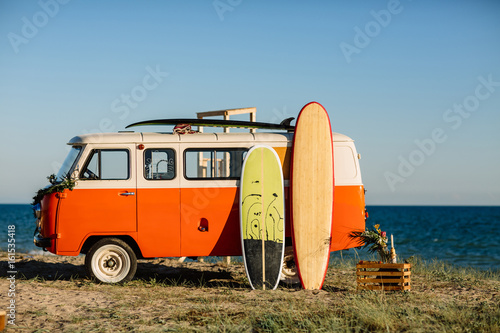 bus with a surfboard on the roof is a parked near the beach Poster