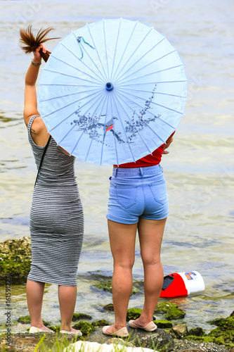 Two girls standing at the waters edge of Tampa bay holding a paper parasol Poster