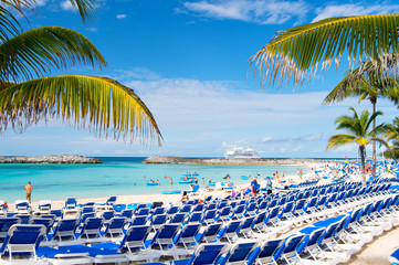 Rows of blue chairs on sea beach with white sand