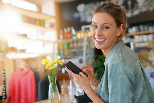 Trendy girl using smartphone while waiting for lunch