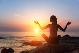 Yoga meditation silhouette. Healthy lifestyle. Fitness woman on the ocean during amazing sunset.