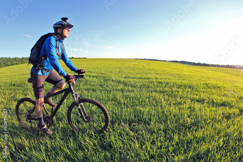 cyclist rides a bicycle on the green field towards the sun