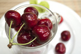 ripe cherry in a glass stands on a white plate