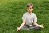 Boy meditating in a park on green grass