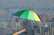 hand holding multicolored umbrella with falling rain at city