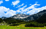 Beautiful view on the high green mountains peaks, on the blue sky background. Mountain hiking paradise landscape, no people.