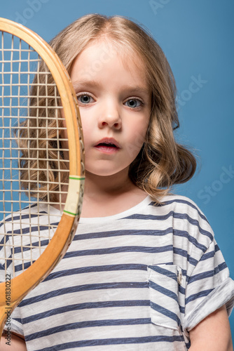 portrait of adorable little girl holding tennis raquet and looking at camera isolated on blue